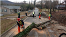 Seven men cutting up fallen tree on street