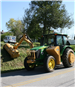 Green and yellow John Deer tractor grading street