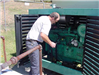 Man servicing green machinery outside