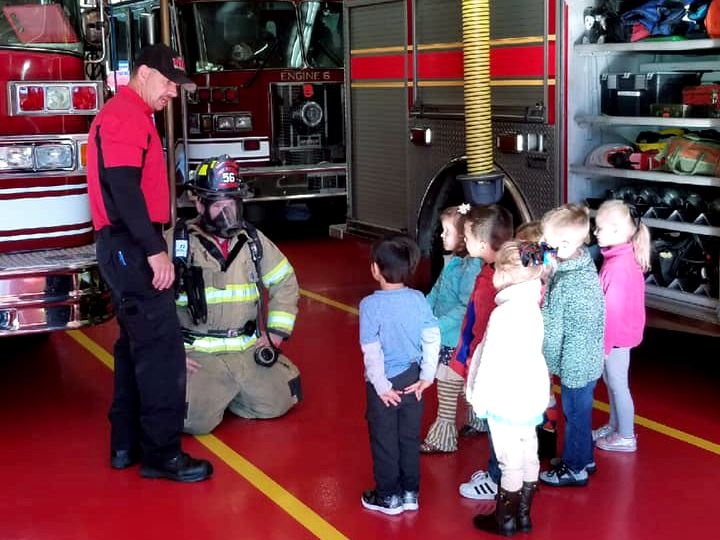 Engineer Billy Safford and Firefighter Jordan Hall talk to children about fire gear