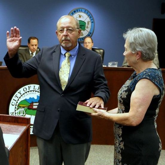 Judge Robert Brady gives the Oath of Office to Ralph Prestwood while Jane Prestwood holds a Bible