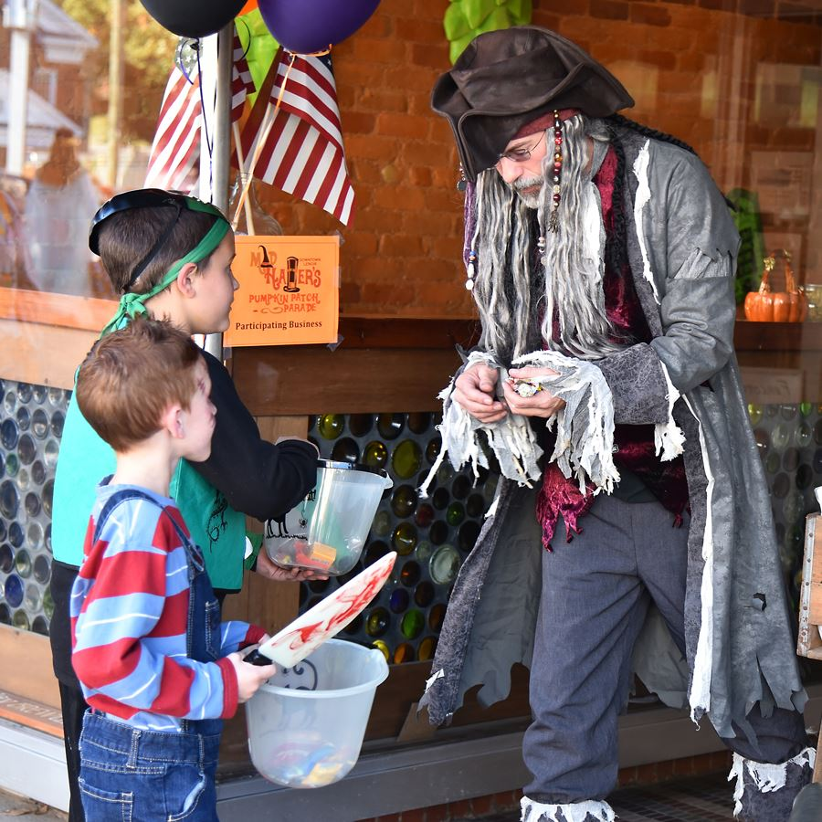 Trick-or-treaters get candy from a pirate in front of Fercott Fermentables in Downtown Lenoir