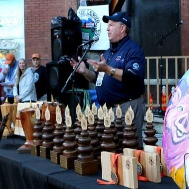 Mayor Joe Gibbons stands behind a table of trophie during the 2018 Smoking In The Foothills festival