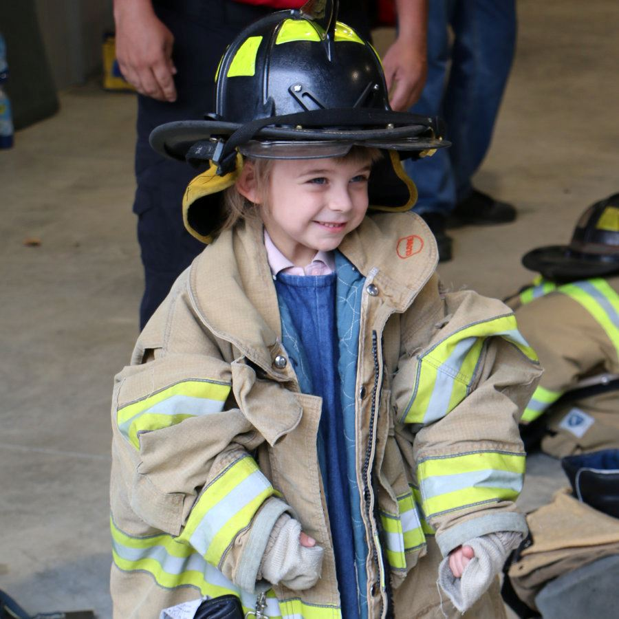A little girl tries on fire gear during the Station 3 open house in Lenoir