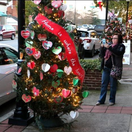A lady takes a photo of a Christmas tree during Light Up Lenoir in Downtown Lenoir, Nov. 16, 2018