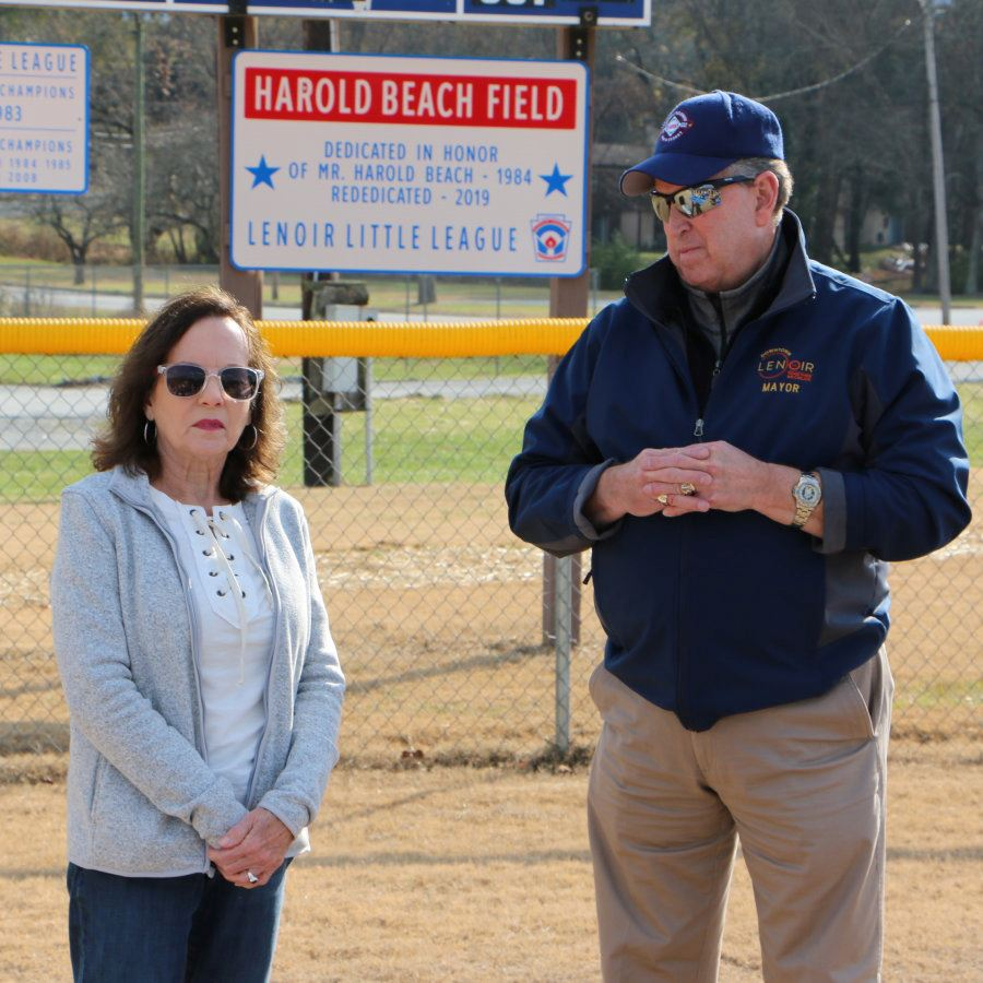 Carol Austin and Joe Gibbons stand in front of the Harold Beach sign at Lenoir Optimist Park