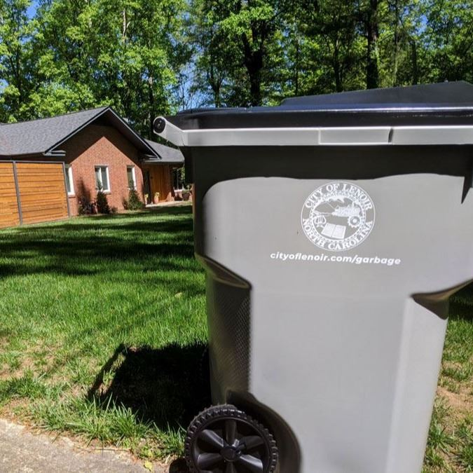A new City of Lenoir garbage cart in front of a house in the city