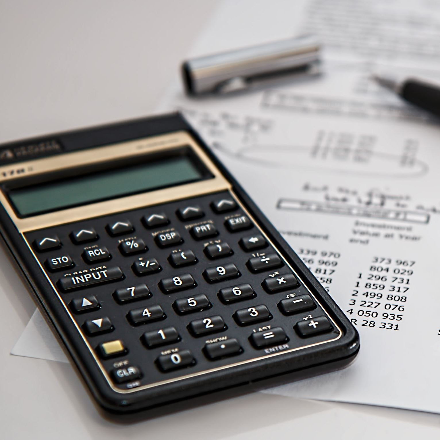 Calculator and pen on top of financial document