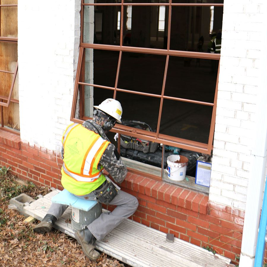 A construction worker paints the metal windows at the new Blue Bell apartments.