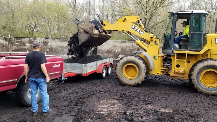 Bobcat loading compost into red truck