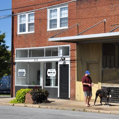 A man walking a dog outside of 818 Harper Ave in downtown Lenoir