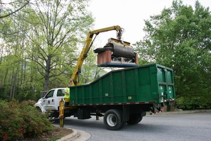 Garbage truck with crane lifting large debris