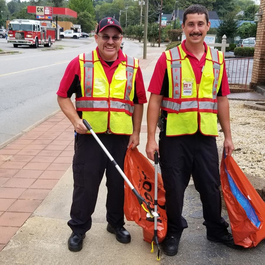 Two City of Lenoir Firefighters pick up litter on Harper Avenue in Lenoir