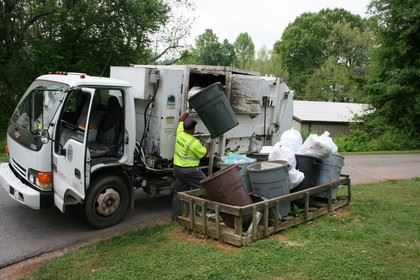 Man picking up trash and putting it into garbage truck