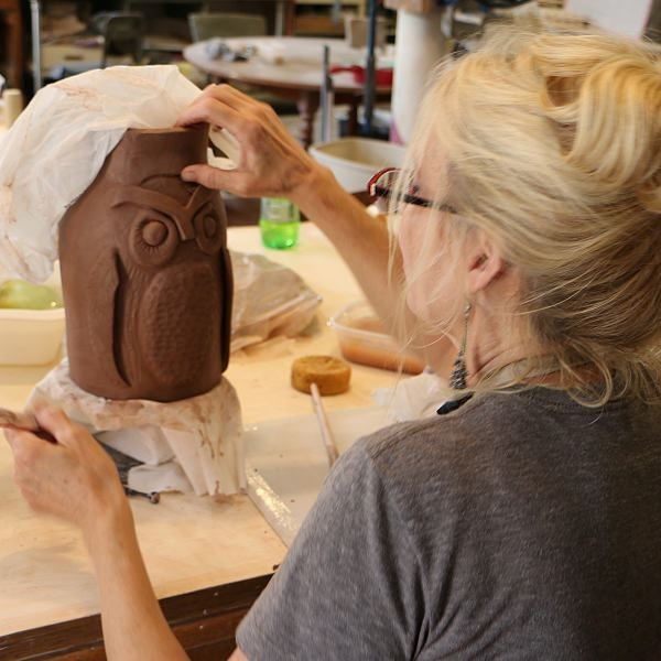 A women is working on an owl pot in pottery class