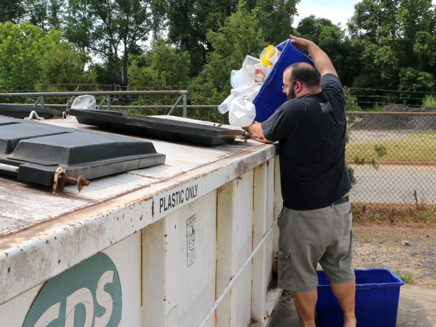 A man dumps plastic containers into a bin at the Recycling center