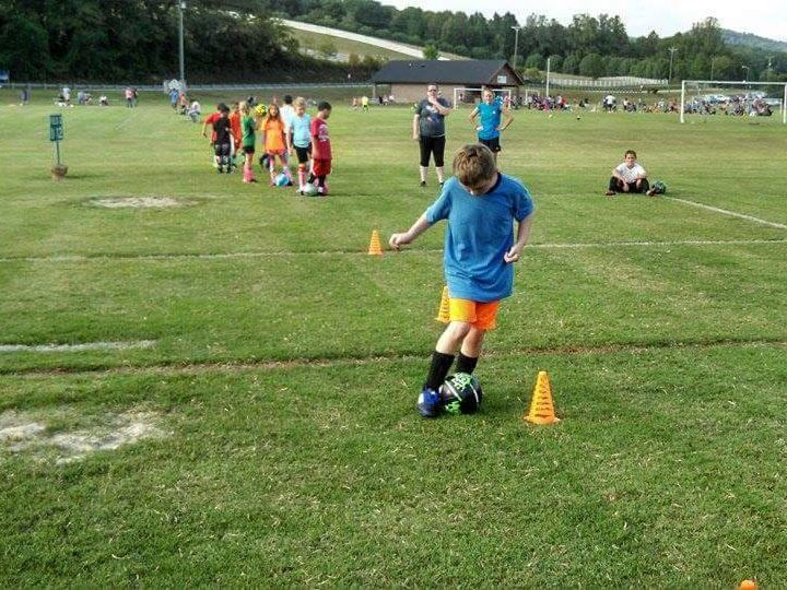 A boy kicks a soccer ball around a cone at the Lenoir Rotary Soccer Complex in Lenoir