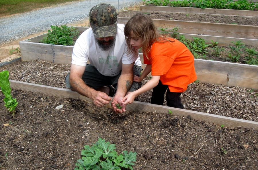 Father and daughter gardening at the Community Gardens on College Avenue in Lenoir