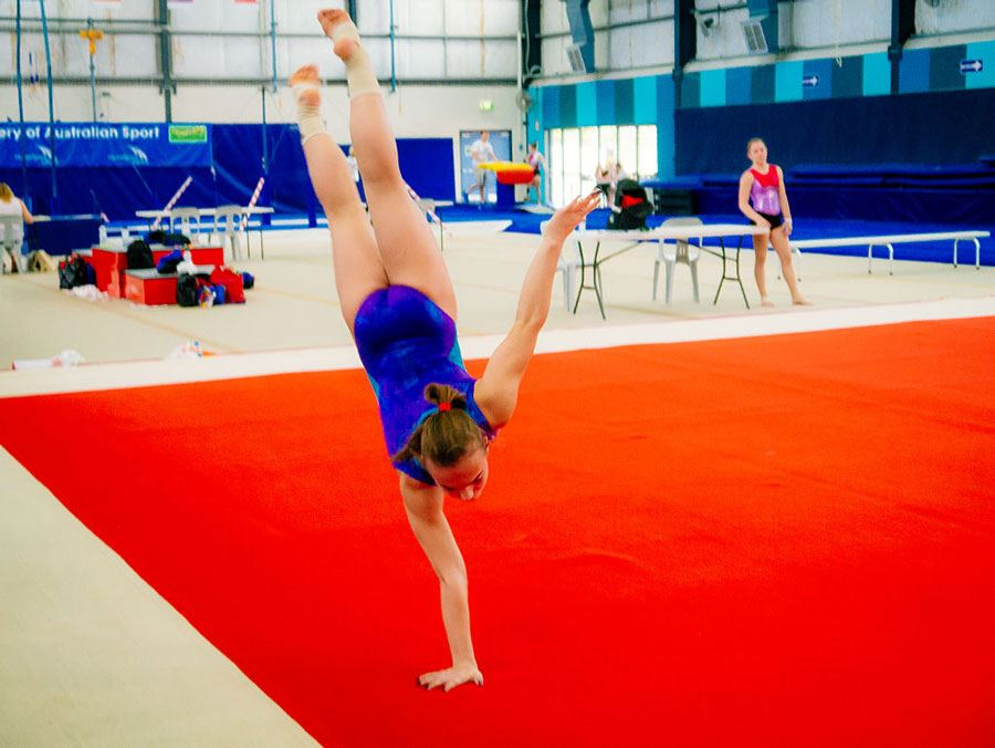 Girl doing single handstand on gymnastics mat