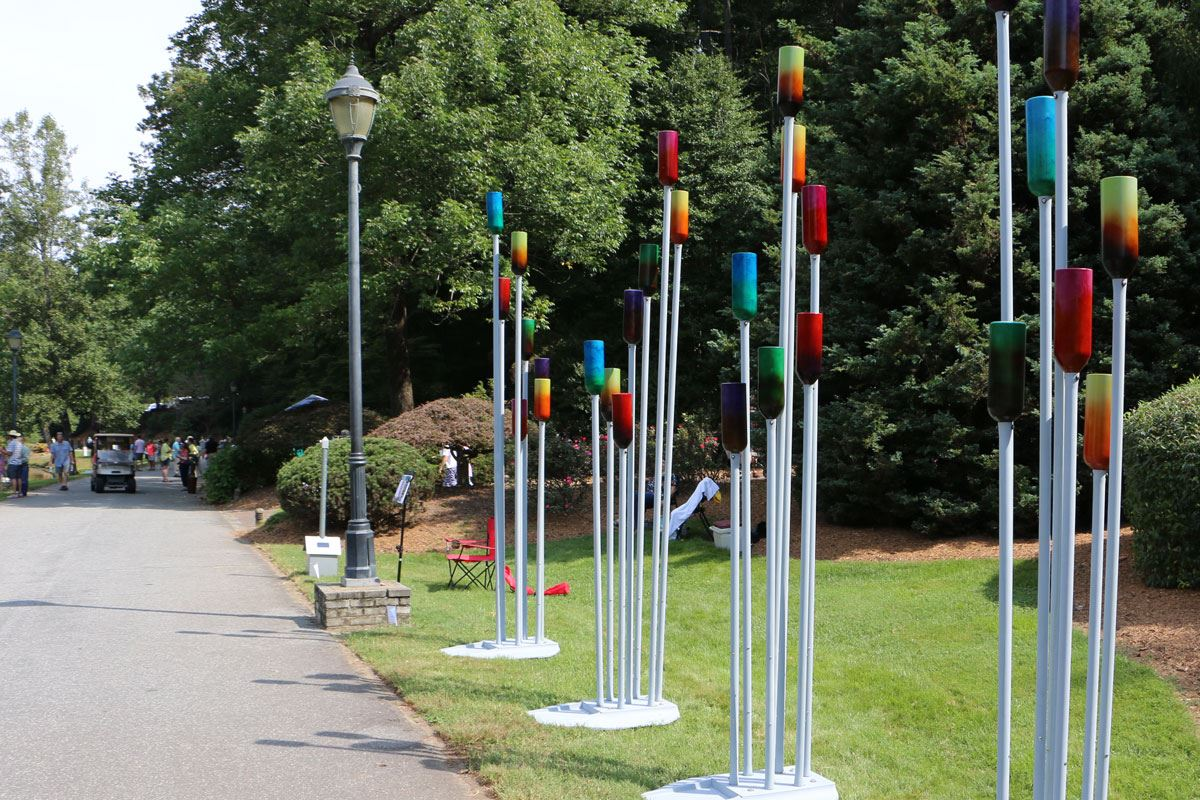 Sculpture of painted bottles on metal posts during the 2018 Sculpture Celebration in Lenoir