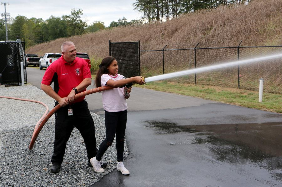 Deputy Kenny Nelson helps a girl operate a fire hose during the Station 3 open house.