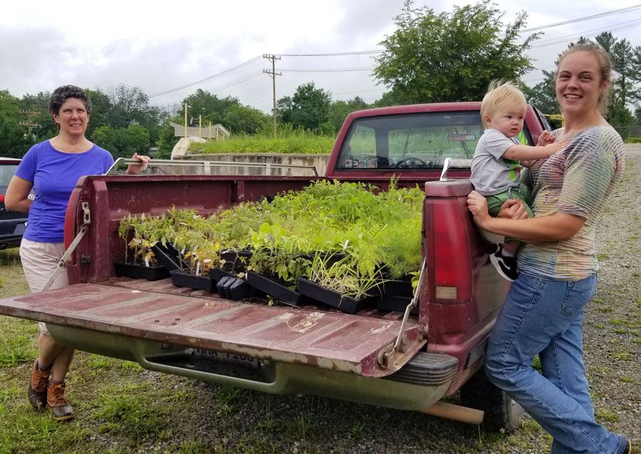 Brandy Richthammer, her son Gray, and Ellen Roberts stand by a truckload of plants,, Friday, May 29,