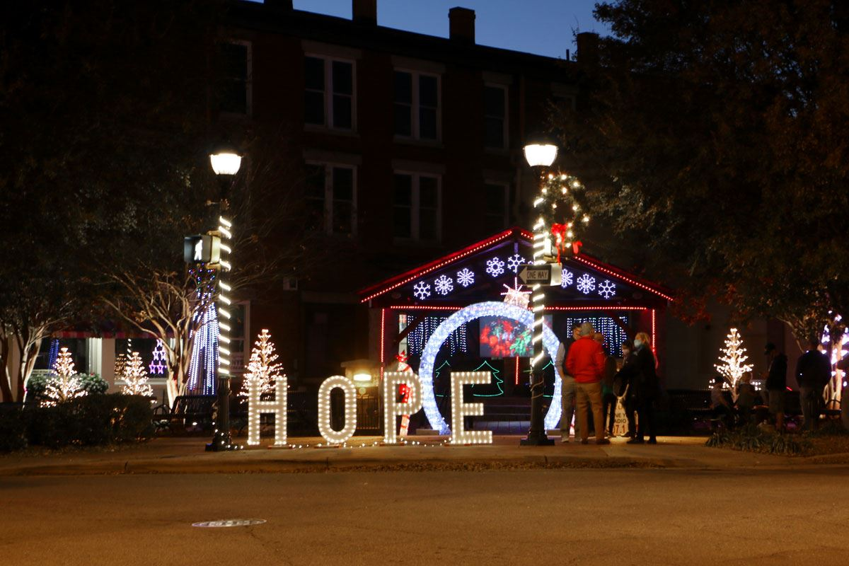 A small group stands in front of the Hope Shines Brightly decorations in Downtown Lenoir.