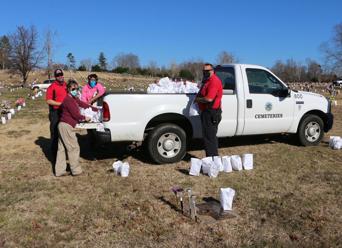 City of Lenoir staff place LED candles in luminaries at Blue Ridge Memorial Park