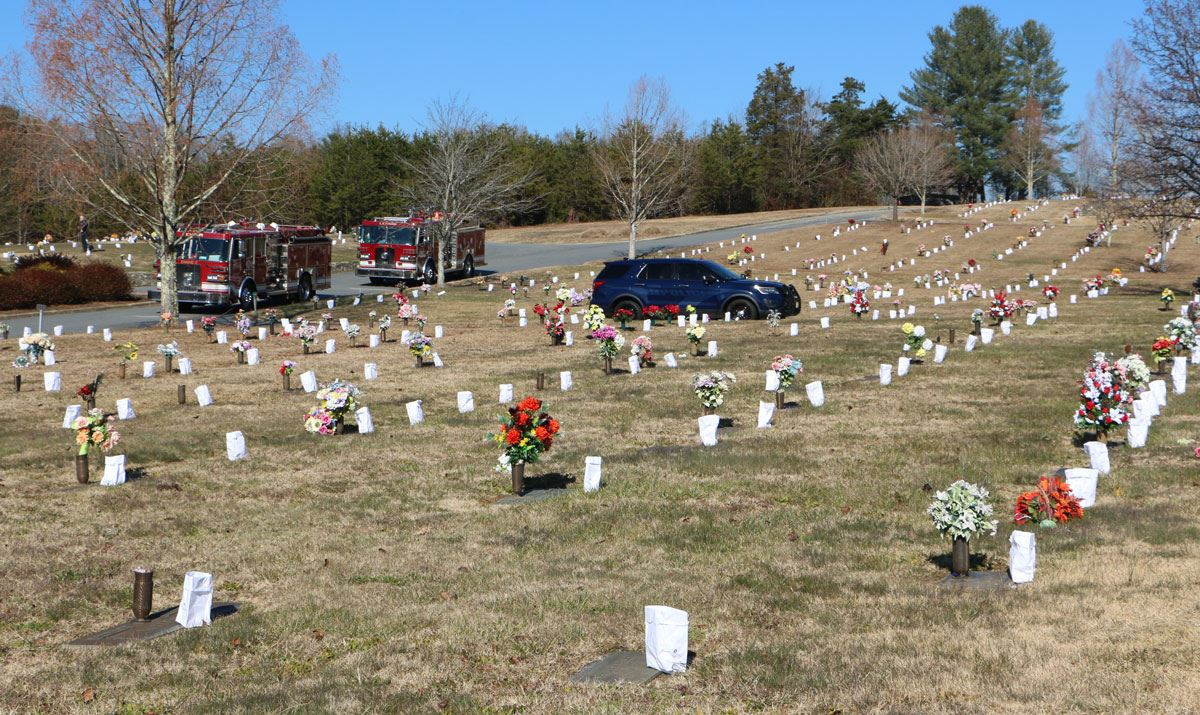 A picture of the cemetery showing luminaries and police and fire vehicles in the background