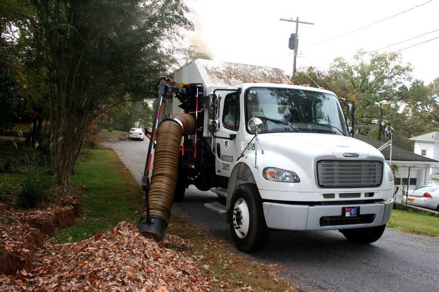 Truck performing leaf pickup