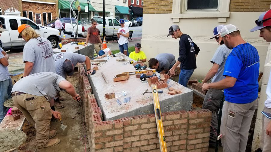 Local high school masonry students brick the cores of the Charters of Freedom in Downtown Lenoir